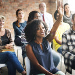 People listen to presentation as one person raises hand