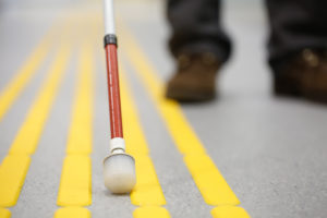 Blind pedestrian walking and detecting markings on tactile paving with  cane
