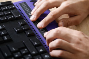Hands rest on braille output device