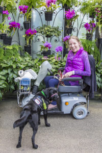 A woman sits in a scooter with a black dog standing in front of her and wearing a vest